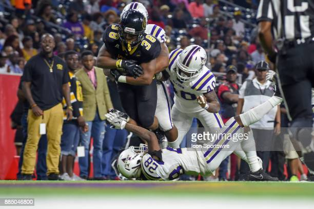 Grambling State Tigers running back Dre' Fusilier is wrapped up by Alcorn State Braves defensive lineman Sterling Shippy during the SWAC Championship...