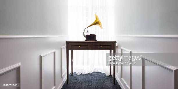 gramophone on table amidst walls at home - gramophone stock pictures, royalty-free photos & images