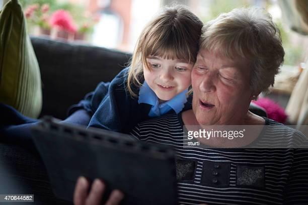 gran and granddaughter looking at a digital tablet .