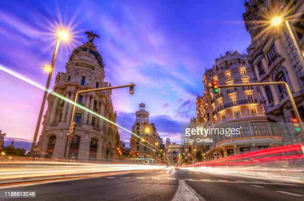 gran via in madrid at sunset with car light trails. spain - madrid stock pictures, royalty-free photos & images