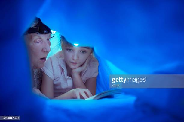 gran with a headtorch bedtime story - british granny stock photos and pictures