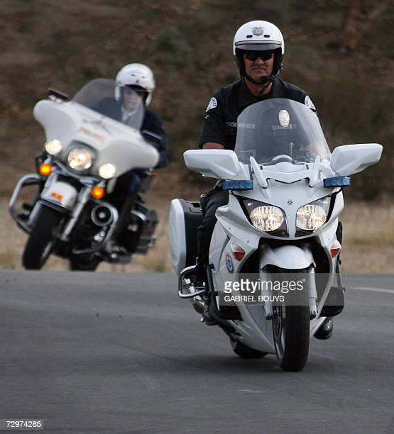 A French police officer rides the Harley Davidson motorcycle of the LAPD before an LAPD officer riding the Yamaha of the French police at the Davis...