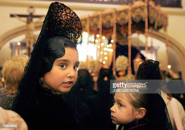 Girls dressed in a traditional mantilla wait in the church 04 April 2007 for the start of the 'Cristo de los gitanos' brotherhood procession in...