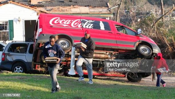 Granadas Baker Jr Quantivous and Kiara Slater remove items from Slater's parents home after a tornado struck in Beauregard Alabama on March 4 2019...