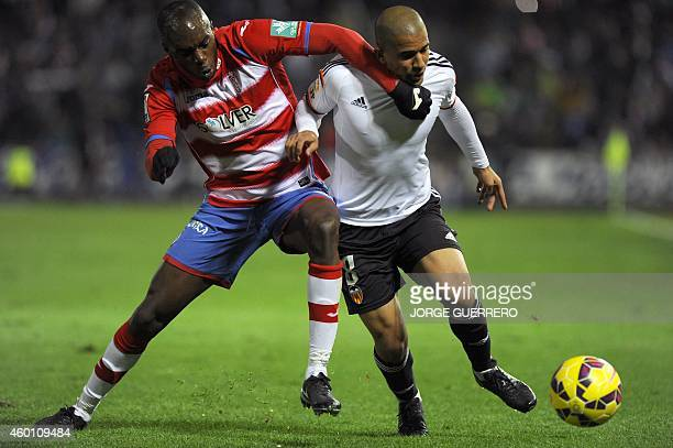 Granada's Cameroonian defender Allan Nyom vies with Valencia's French midfielder Sofiane Feghouli during the Spanish league football match Granada CF...