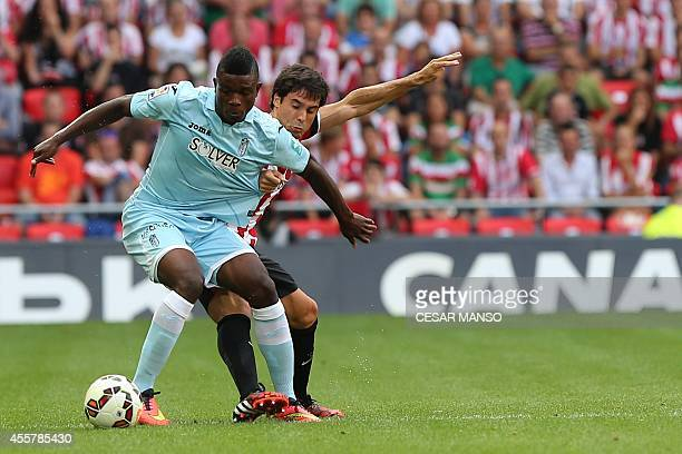 Granada's Colombian forward Jhon Andres Cordoba vies with Athletic Bilbao's midfielder Unai Lopez during the Spanish league football match Athletic...