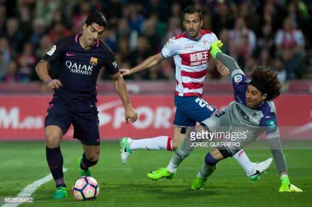 Granada's French defender Matthieu Saunier and Mexican goalkeeper Guillermo Ochoa vie with Barcelona's Uruguayan forward Luis Alberto Suarez during...