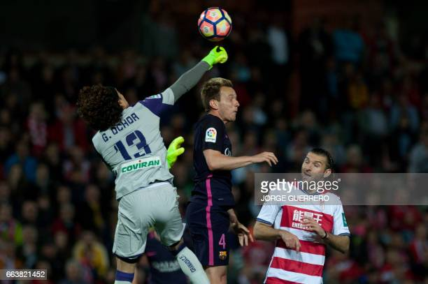 Granada's Mexican goalkeeper Guillermo Ochoa and Uruguayan defender Gaston Silva vies with Barcelona's Croatian midfielder Ivan Rakitic during the...