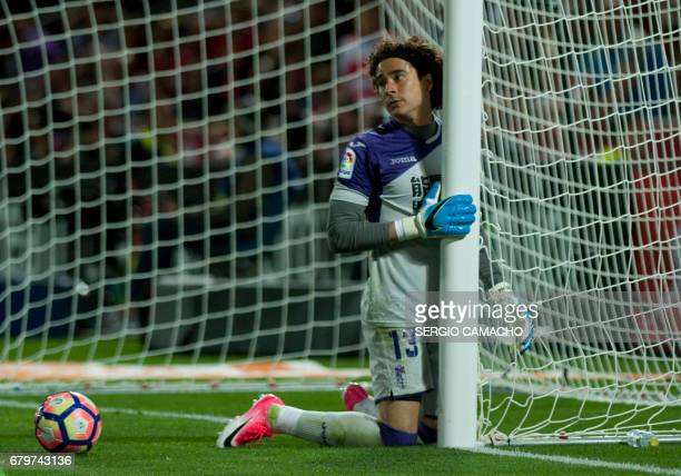 Granada's Mexican goalkeeper Guillermo Ochoa kneels under the goal's net during the Spanish league football match Granada FC vs Real Madrid CF at...