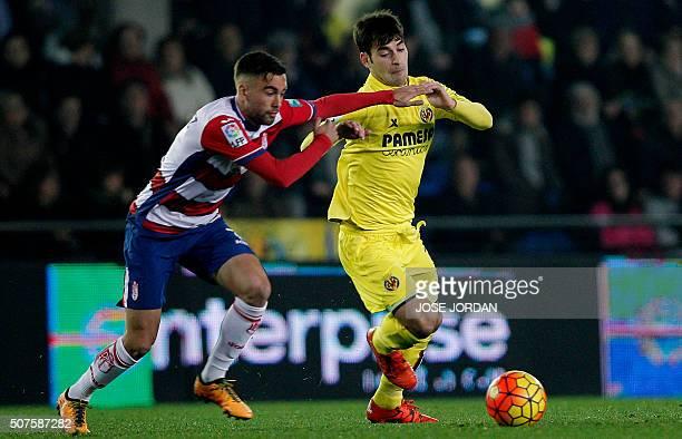 Granada's midifelder Rober Ibanez vies with Villarreal's midfielder Manu Trigueros during the Spanish league football match Villarreal CF vs Granada...