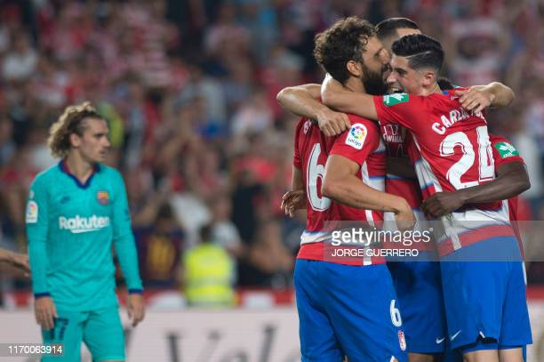 Granada's players celebrate their win at the end of the Spanish league football match between Granada FC and FC Barcelona at Nuevo Los Carmenes...