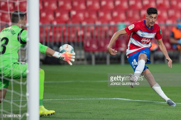 Granada's Spanish forward Carlos Fernandez shoots to score a goal during the Spanish League football match between Granada and Getafe at the Los...