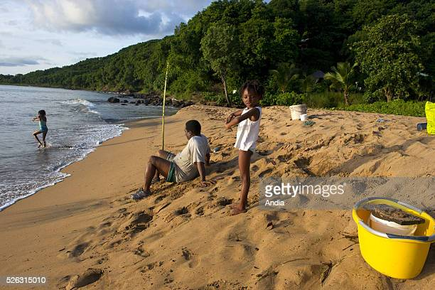 Grand Anse Beach Deshaies BasseTerre Island Guadeloupe Family fishing on foot on the sand at the water's edge