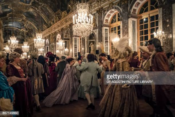 Grand ball in the Hall of Mirrors courtship party with participants wearing clothes from the Louis XIV period Palace of Versailles France Historical...
