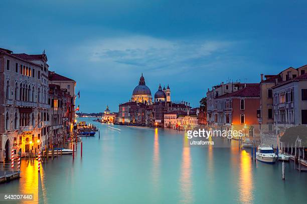grand canal and santa maria della salute at dusk - punta della dogana stock photos and pictures