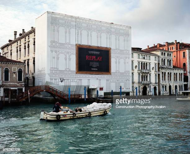 Grand Canal venice with Replay building under scaffolding with boat carrying goods