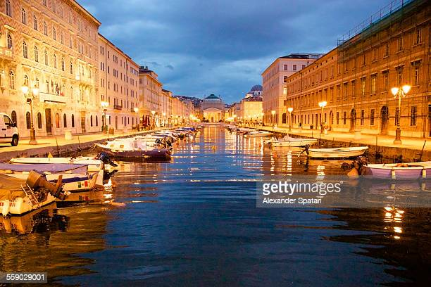 Grand canal with boats at night in Trieste, Italy