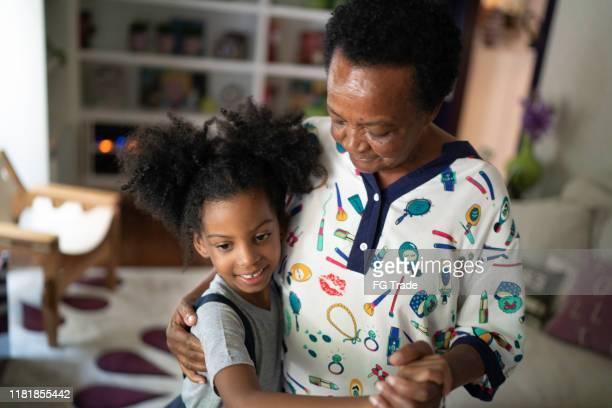 grand dochter en grootmoeder dansen in de woonkamer - gewalt stockfoto's en -beelden