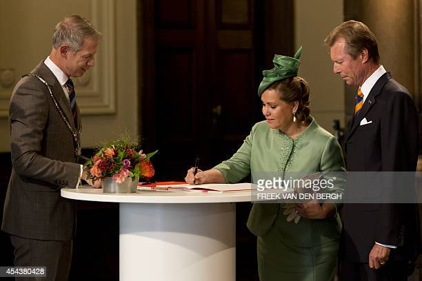 Grand Duchess Maria Teresa and Grand Duke Henri of Luxembourg sign a guestbook in the presence of Maastricht mayor Onno Hoes during a ceremony in the...