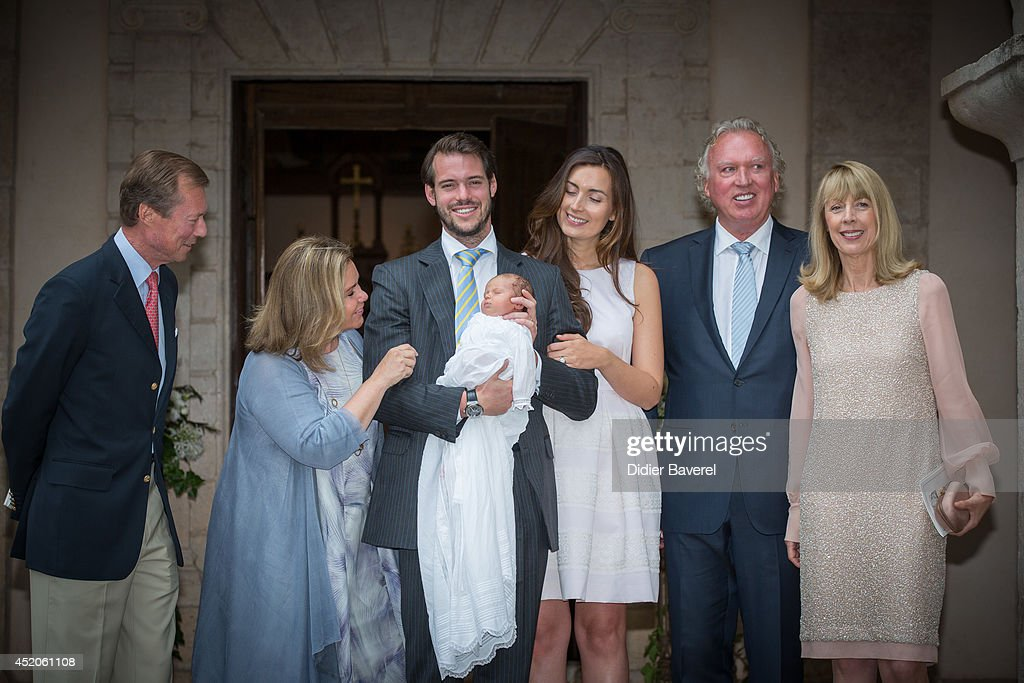 Grand Duke Henri and Grand Duchess Maria-Teresa of Luxembourg, pose with their son Prince Felix holding his daughter Princess Amalia, and his wife Princess Claire of Luxembourg, center, with Hartmut and Gabriele Lademacher, at right, parents of Claire of Luxembourg, after the baptism ceremony of Princess Amalia, at the Saint Ferreol Chapel in Lorgues on July 12, 2014 in Lorgues, France.