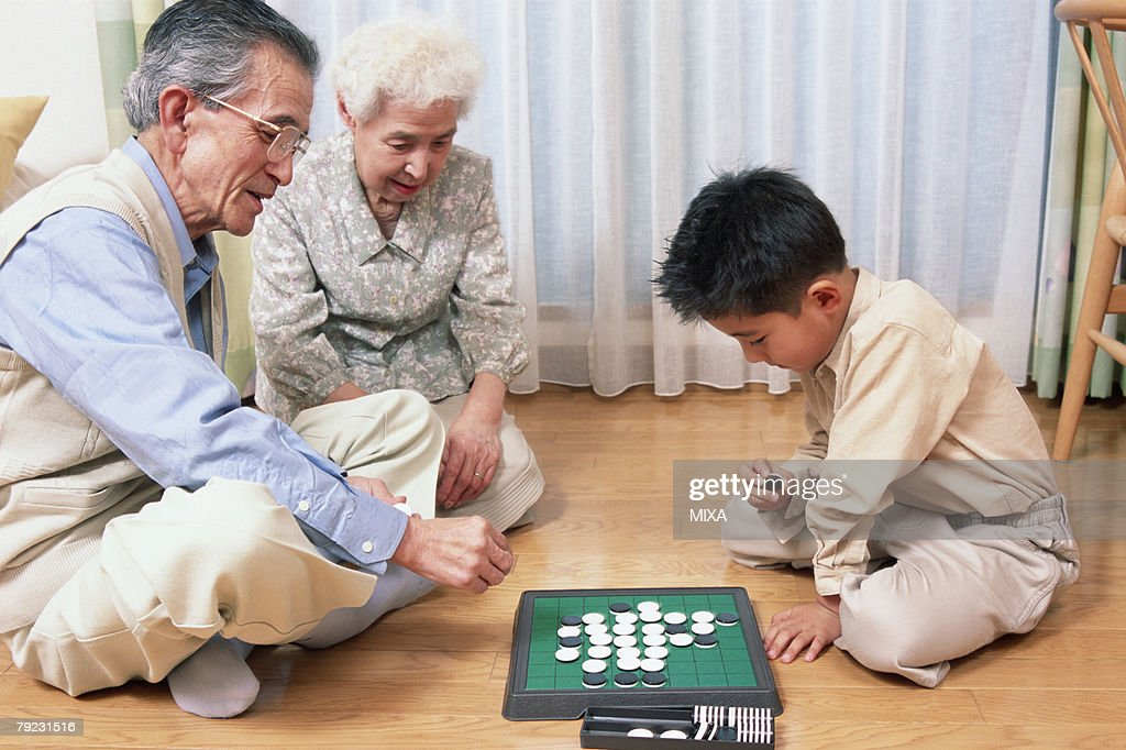 A grand father and a grand child playing with game : Stock Photo