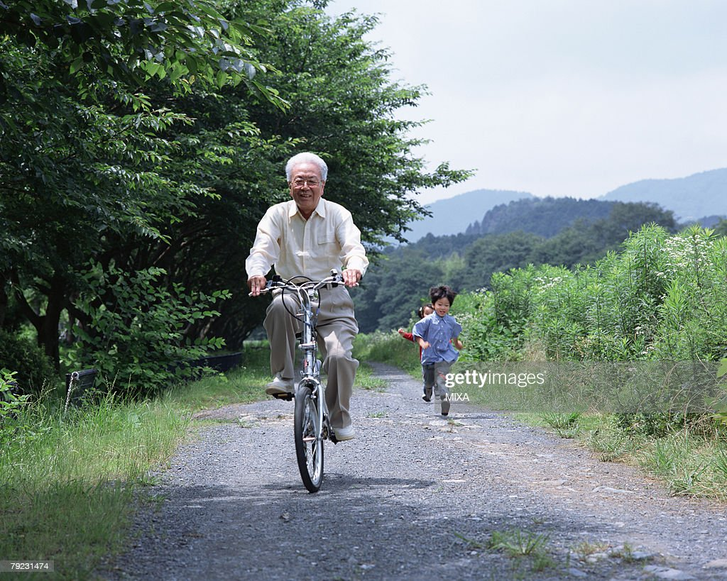 A grand father riding a bicycle : Stock Photo
