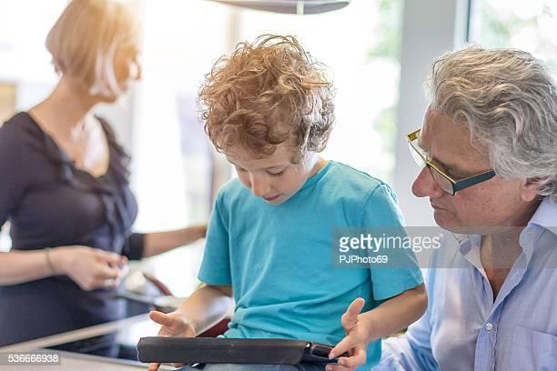 grand father using digital tablet with his nephew - pjphoto69 bildbanksfoton och bilder