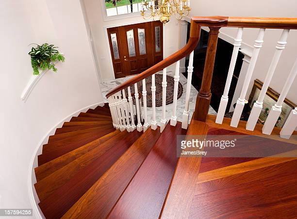 grand foyer down beautiful winding hardwood staircase in showcase home - hardwood stock pictures, royalty-free photos & images