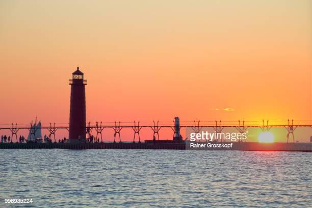 grand haven pier lighthouse (1905) on lake michigan at sunset - rainer grosskopf 個照片及圖片檔