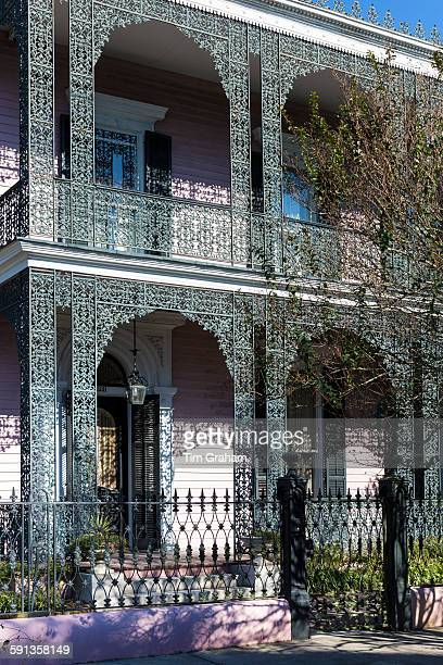 Grand mansion house with ornate lacy ironwork fretwork double gallery in the Garden District of New Orleans Louisiana USA