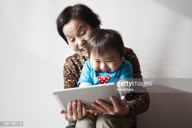 Grand mother and grand son using a digital tablet together