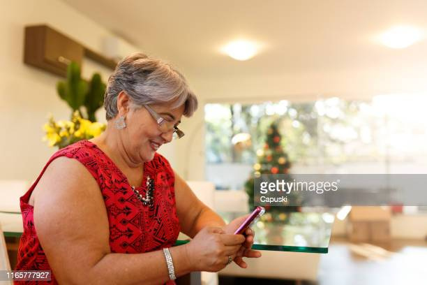 grand mother send marry christmas on smart phone - fat granny stock pictures, royalty-free photos & images