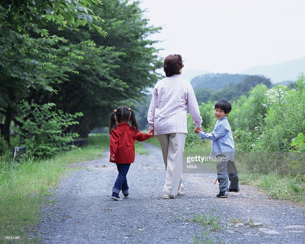 A grand mother walking with grand children : Stock Photo
