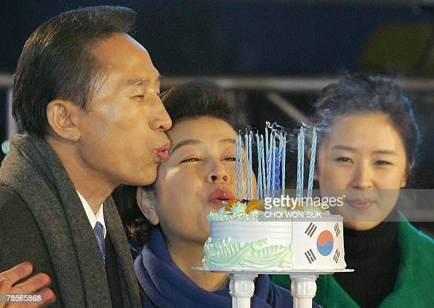 Grand National Party presidential candidate Lee MyungBak is helped by his wife Kim YunOk to blow out the candles of his birthday cake presented to...