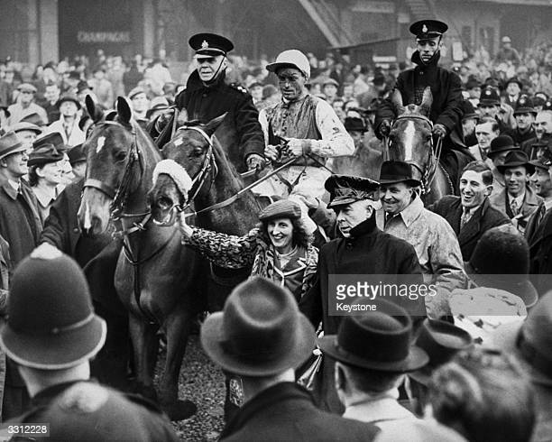 Grand National winner 'Caughoo' ridden by Eddie Dempsey is led towards the winners' enclosure after the race at Aintree