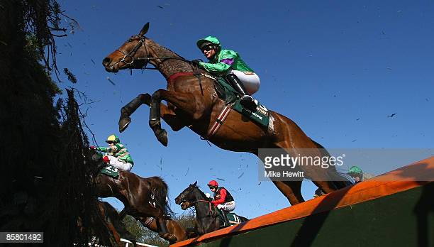 Grand National winner Mon Mome with jockey Liam Treadwell jump the open ditch on their way to victory during the John Smiths Grand National at...