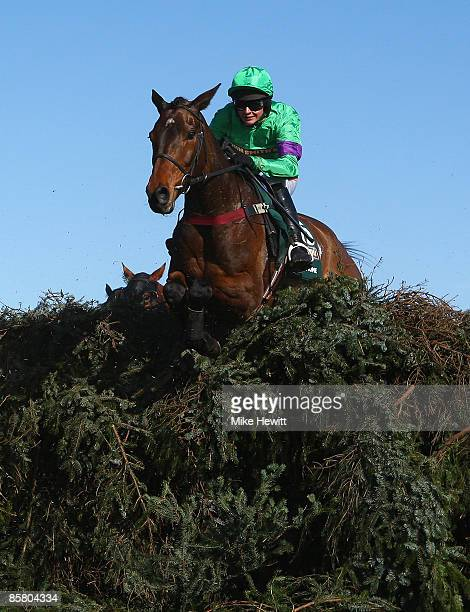 Grand National winner Mon Mome with jockey Liam Treadwell jumps the open ditch on their way to victory during the John Smiths Grand National at...