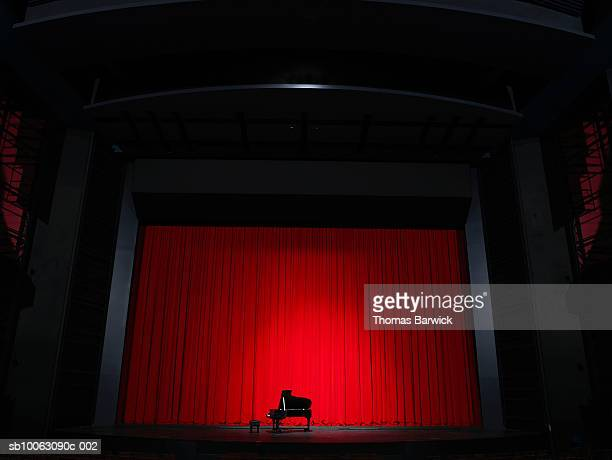 grand piano in spotlight on stage - grand piano stock photos and pictures