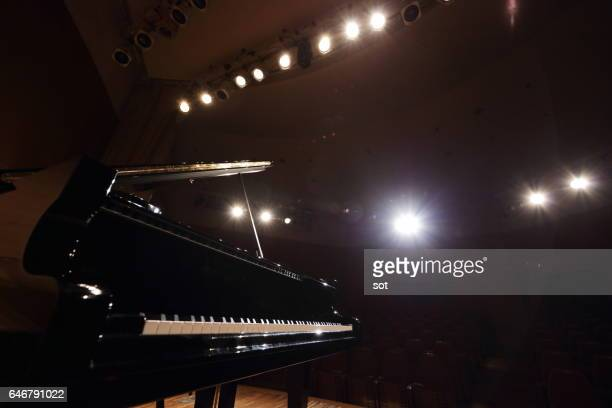 grand piano on concert hall stage - grand piano stock photos and pictures