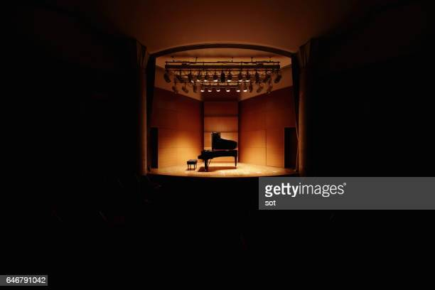 grand piano on concert hall stage - concert hall stock pictures, royalty-free photos & images