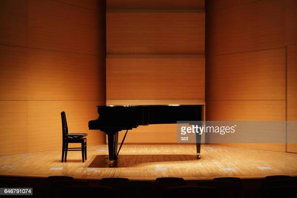 grand piano on concert hall stage - grand piano stock pictures, royalty-free photos & images
