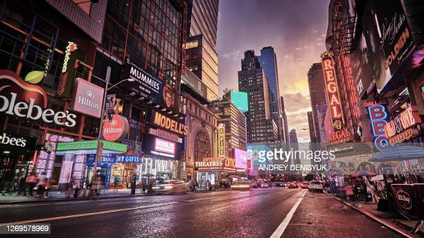grand shine of 42nd street. new york. classical view of times square. illuminated advertisement billboards. dramatic sunset. - times square manhattan stock pictures, royalty-free photos & images