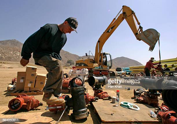 Grand Terrace June 18 2007 – Everardo Ramirez jumps on a wrench while working on a water pipe joint at a construction site of a master planned...
