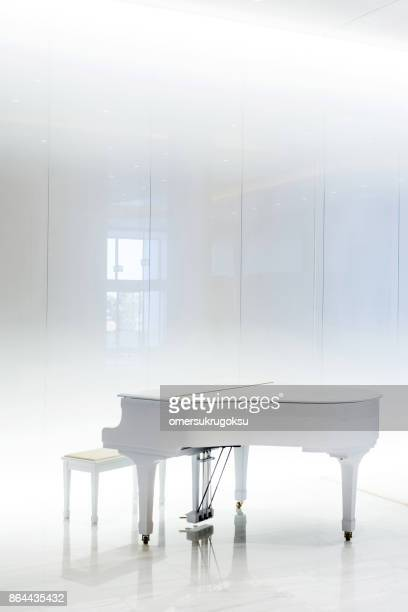 Grand white piano in white interior, Greece
