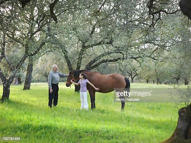 Grandad and granddaughter stroking horse