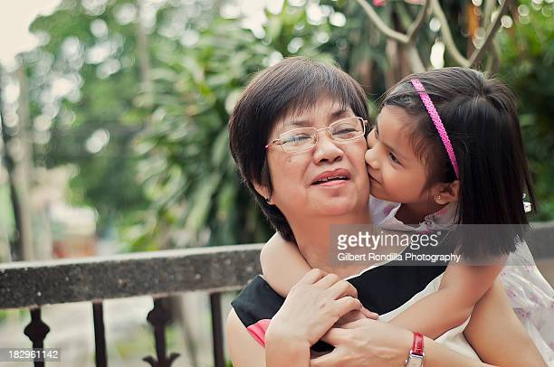 grandaughter kissing grandmother - philippines stock pictures, royalty-free photos & images