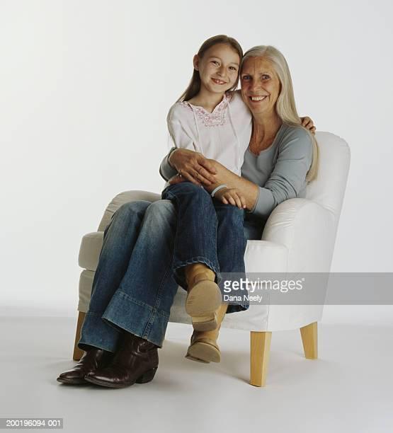 Grandaughter (7-9) sitting on grandmother's lap, smiling, portrait