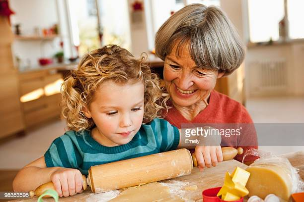 grandchild and grandma rolling dough