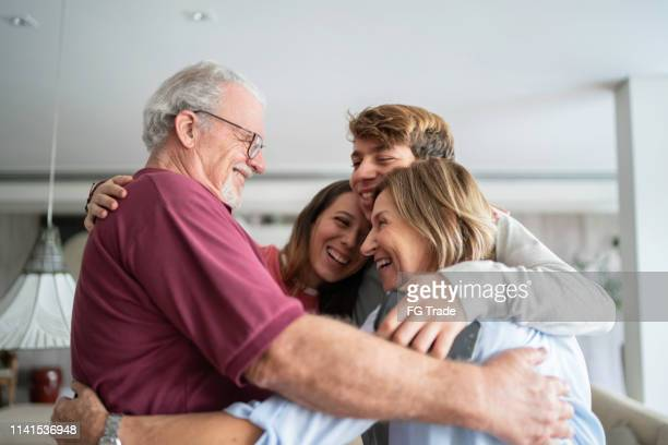 grandchild and grandparents embracing - arm around stock pictures, royalty-free photos & images