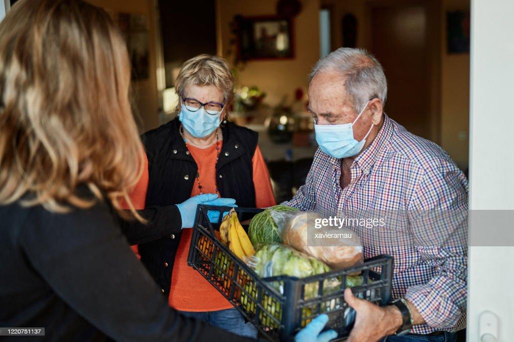 孫は、彼らの家でパンデミック中に祖父母に食料品を提供します : ストックフォト
